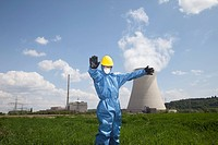 Germany, Bavaria, Unterahrain, Man with protective workwear standing in field at AKW Isar