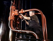 STEEL HYDRAULIC PRESS, 1942.Maintenance man working on a cold steel hydraulic press at the Combustion Engineering Company in Chattanooga, Tennesee. Ph...