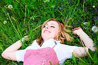 Beautiful country girl in red lay on grass