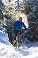 A mountain biker riding through a snowy forest with hyer breath being lit by the sun