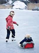 Girl pulling brother on sledge while ice skating on frozen lake