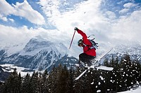 Skier jumping, mountain in background