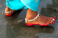 Indian woman's feet decorated with anklet and red color