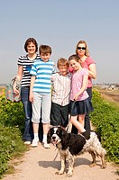 Two sisters and their three children walking the dog on a family country walk in the Uk