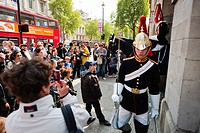 England, London, Whitehall. A large group of tourists watch and take photographs of Guards of the Blues and Royals on duty in Whitehall.