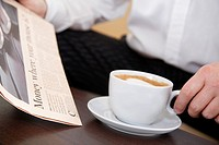 Man sat, reading a newspaper and holding a cup of Cappuccino