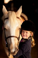 Caucasian girl standing with horse
