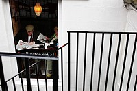 Scotland, City of Edinburgh, Edinburgh. A couple reading newspapers in a cafe on Hanover Street