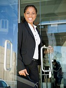 African American businesswoman opening office door
