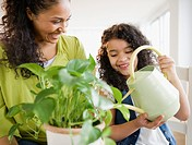 Mother and daughter watering plant together