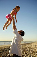 Father lifting daughter in air on beach
