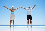 Senior couple standing at edge of infinity pool with arms outstretched (thumbnail)