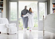 Couple in bathrobes standing in balcony doorway