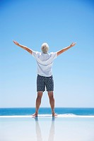 Senior man with arms outstretched at edge of infinity pool