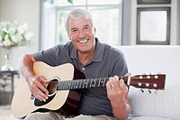 Senior man playing guitar in living room