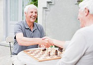 Senior men playing chess on patio