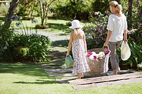 Grandmother and granddaughter carrying basket of flowers