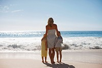 Mother and daughters on beach looking at ocean