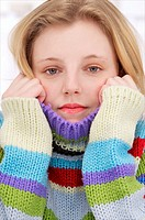 Young woman holding her multicolored pullover over her chin and ears or cold or aching ears