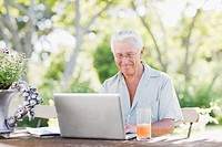 Senior man using laptop at patio table