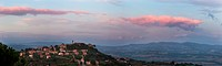 Panorama view of medieval hilltop town of Monte Castello di Vibio, at sunset, with spectacular pink clouds, skyscape, Umbria, Italy