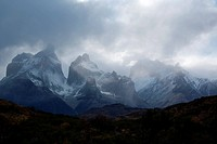 Snow covered Los Cuernos mountains with dramatic autumn cloudscape, fall colours of trees in foreground, Torres del Paine, Southern Chile, Patagonia