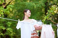 Woman drying laundry, smiling and looking away