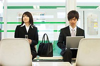 Businessman and businesswoman waiting in train station