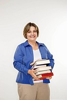 Caucasian middle aged woman holding stack of books.
