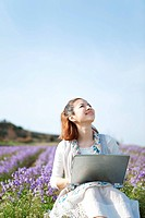 Young woman using laptop in front of flowers