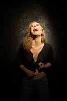 Dark portrait of sexy Caucasian mid_adult woman with head back laughing.