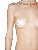 Mid section view of a naked woman with adhesive bandage on her nipples