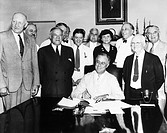 President Franklin D. Roosevelt signing the Social Security Act in the Cabinet Room of the White House, 14 August 1935, flanked by the bill´s co_autho...