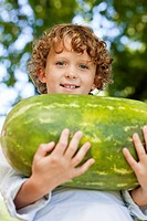 Close-up of smiling boy holding watermelon (thumbnail)