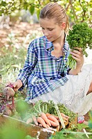 Girl choosing vegetables from a crate