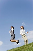 Businesswomen jumping into air
