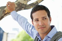 Close_up of a mid adult man holding a branch of tree