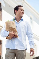 Mid adult man holding a paper bag full of vegetables and smiling