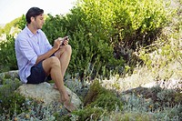 Mid adult man sitting on a rock and listening to music with an MP3 player (thumbnail)