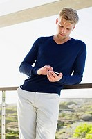 Young man using a mobile phone at a balcony (thumbnail)