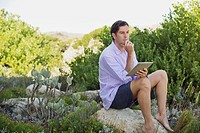 Man sitting on a rock using a digital tablet and thinking