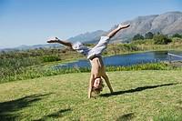 Cute little boy doing cartwheel against mountain