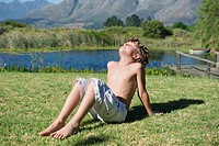 Shirtless little boy sitting with his eyes closed against mountain