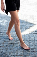 Low section view of a young woman walking bare feet on cobbled street