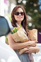 Portrait of a beautiful young woman holding paper bags full of vegetables