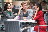 Three young friends talking on mobile phones in a restaurant