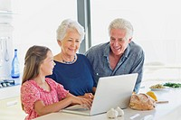 Girl using a laptop with her grandparents looking at her in a kitchen