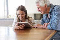 Girl using a digital tablet with her grandfather sitting near her