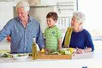 Senior couple preparing food with their grandson