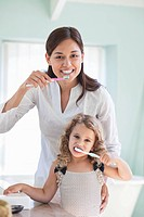 Portrait of a young woman and her daughter brushing teeth (thumbnail)